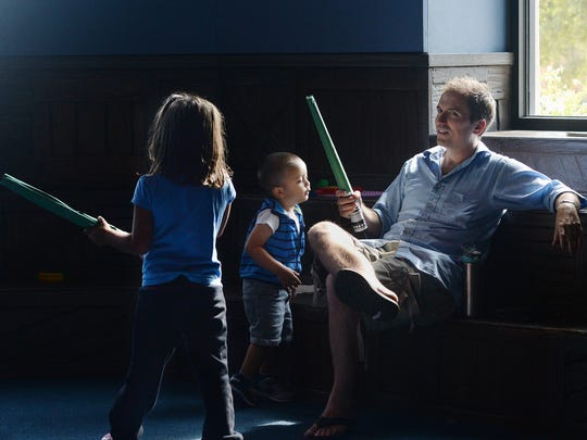 """Mike Heithaus and his kids, Bela, left, and Shay, play with """"Star Wars"""" items at the Camarillo Library on Saturday."""