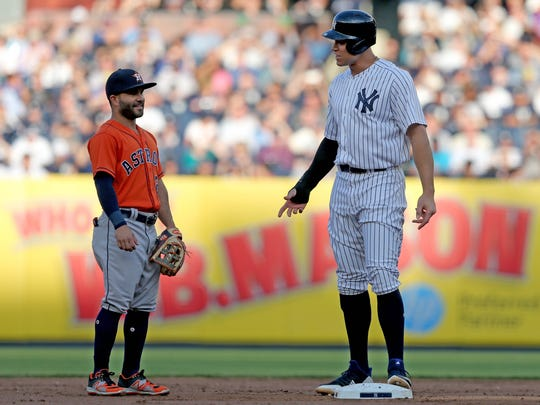 New York Yankees right fielder Aaron Judge (99) talks to Houston Astros second baseman Jose Altuve (27) after reaching second base during the first at Yankee Stadium.