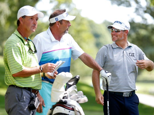 Marc Kiser, the owner of Advertising Plus, talks with pro golfer Michael Arnaud (right) and his caddie at Highland Springs Country Club during the Price Cutter Charity Championship Pro-Am on Wednesday, July 25, 2018.