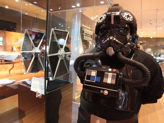 "An Imperial TIE fighter pilot stands next to a model of a TIE fighter on May 21, 2013, in a display at the Indiana State Museum to publicize ""Star Wars""-themed exhibitions there."