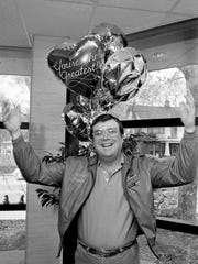 """Norro Wilson, head of Merit Music's Nashville operation, beams beneath a balloon that proclaims him """"the greatest"""" as he hams it up in the company's brand-new headquarters at 66 Music Square West on April 10, 1985."""
