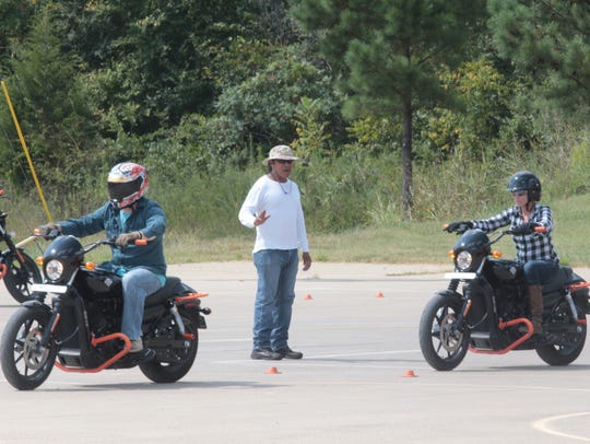 A motorcycle instructor guides new riders through a