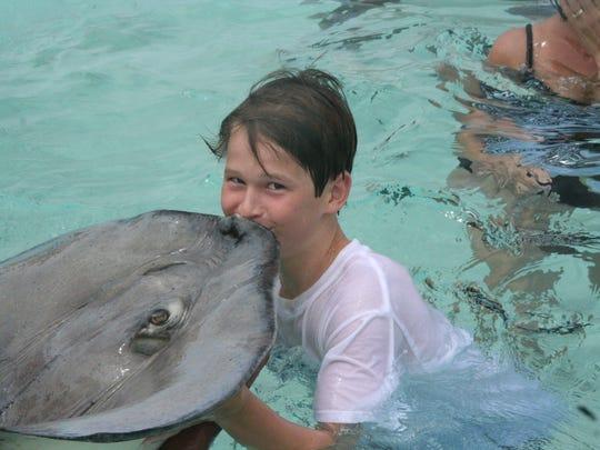 Morgan Williams, son of columnist Ben Williams, kisses a stingray at Grand Cayman.