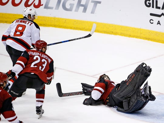 Devils right wing Beau Bennett (8) beats Arizona Coyotes defenseman Oliver Ekman-Larsson (23) and goalie Mike Smith, right, for a goal during the second period of an NHL hockey game Saturday, March 11, 2017, in Glendale, Ariz. The Devils ended up losing this game, for their 10th straight defeat.