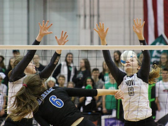 Marian's Lauren Wenzel (6) gets a shot past the outstretched arms of Novi's Savannah Frick (8) in the Class A state final at Battle Creek on Nov. 18.