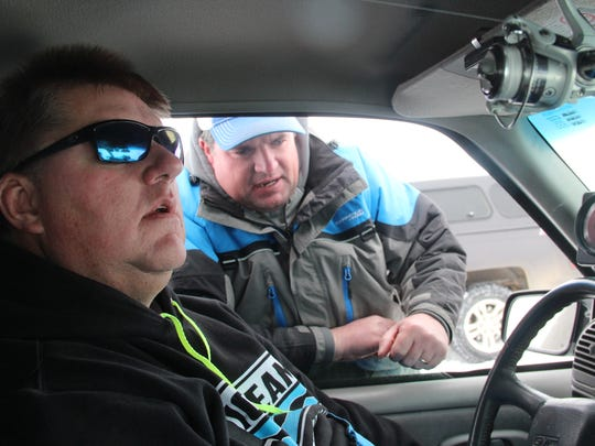 """Steve """"Zippy"""" Dahl, left, and Jason Mitchell, both of Devils Lake, North Dakota, look at a map and discuss options for ice fishing on Devils Lake."""