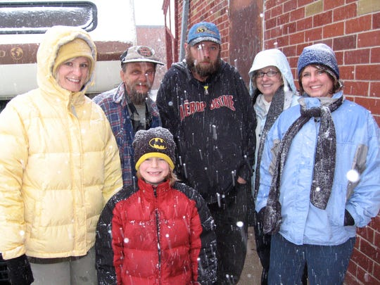 Jacki Stevens, far left, and her son, Caleb, lead a group of volunteers on snowy expeditions to the woods to help warm up the homeless.