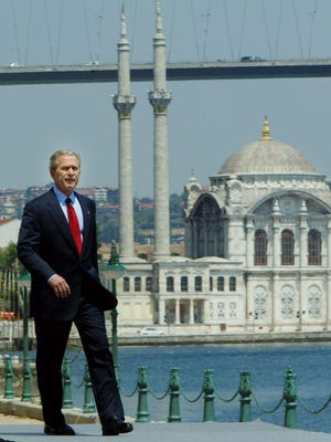 U.S. President George W. Bush walks out on stage before delivering a speech at Galatasaray University June 29, 2004, in Istanbul, Turkey. In the background is Ortakoy Mosque. Bush standing at the historic Bosporus waterway that has long linked Europe and Asia, defended his push for Middle East democracy Tuesday against Arab critics who say the United States seeks to impose its views on the region. (AP Photo/Pablo Martinez Monsivais)