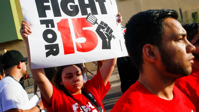 Protesters, activists, and fast food workers march outside McDonalds during a demonstration for an increased minimum wage on Thursday, April 14, 2016, on Seventh Street and McDowell in Phoenix.