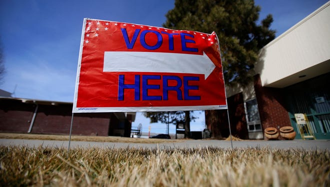 A sign alerting voters to a polling place is display Feb. 13, 2016, in front of Aztec City Hall.