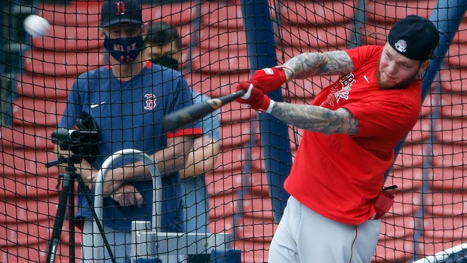 Boston's Alex Verdugo swings as manager Ron Roenicke, left, looks on during Friday's practice at Fenway Park.