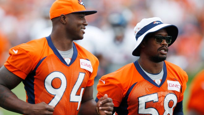 Broncos defensive end DeMarcus Ware, left, and outside linebacker Von Miller run between stations to watch drills at the team's NFL football training camp on Aug. 3 in Englewood, Colo.