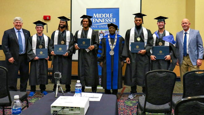 Ahead of the Camellia Bowl, MTSU holds a special graduation ceremony for five football players at the Embassy Suites hotel in Montgomery, Ala., on Dec. 15, 2017. From left to right: MTSU athletic director Chris Massaro, holder Jim Cardwell, defensive back Mike Minter, defensive back Charvarius Ward, MTSU president Sidney McPhee, defensive end Jahmal Jones, quarterback Brent Stockstill, MTSU coach Rick Stockstill.