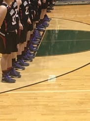 The Marshall girls basketball teams wears purple laces