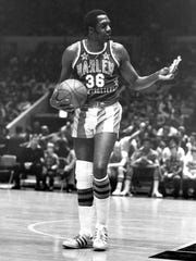 "FILE - In this Feb. 18, 1978, file photo, Meadowlark Lemon, of the Harlem Globetrotters basketball team, offers a pretzel to a referee during a game at New York's Madison Square Garden. Lemon, known as the Globetrotters' ""clown prince"" of basketball, died Sunday, Dec. 27, 2015, in Scottsdale, Ariz. He was 83. (AP Photo/Suzanne Vlamis, File)"