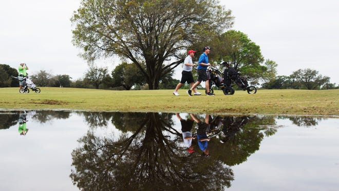 From left, Jacob Steininger, Charlie Webb and Jim McCormack are reflected in a puddle at the Fort Myers Country Club while playing a round of golf earlier this year.