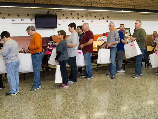 Volunteers line up to have gift bags filled with clothes