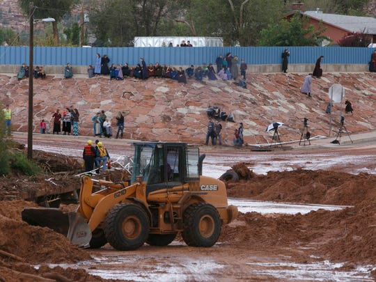 Residents of the town towns of Hildale and Colorado City watch efforts to remove debris from a bridge at the intersections of Arizona and Central streets in Colorado City on Tuesday, Sept. 15, 2015.
