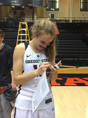 OSU guard Katie McWilliams signs autographs after a recent game at Gill Coliseum.