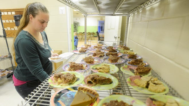 Samantha Carson puts slices of pie into to-go containers during the Salvation Army's Thanksgiving community dinner on Wednesday. Carson volunteers at the Salvation Army after the charity helped her when she arrived in Zanesville with nowhere to live and an infant daughter.