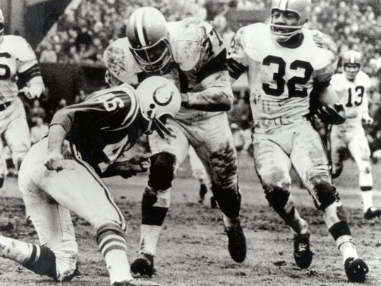 Dick Schafrath throws a block for Jim Brown in the