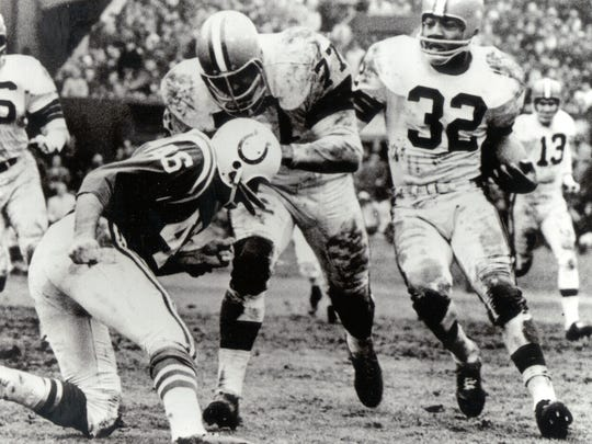Dick Schafrath throws a block for Jim Brown in the 1964 NFL Championship Game against the heavily-favored Baltimore Colts, won by the Browns 27-0. In his day, Brown owned Cleveland, the way Cavs superstar LeBron James does now after giving the city its first major title in 52 years.