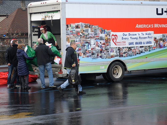 Volunteers empty out a truck with bags of Christmas