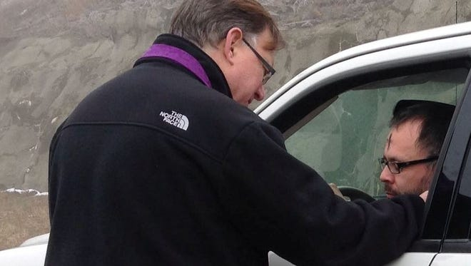 The Rev. Mack Strange blesses someone after imposing ashes on the person's forehead during a drive-through Ash Wednesday blessing service at a location where Strange served as pastor.