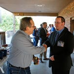 Democrat Sean Feeney, center, greets voters during at the Mount Airy Civic Club steak fry this month. Party leaders tried to convince him to drop out of the race when his opponent, Chris Monzel, suddenly seemed vulnerable, but refused to step aside.