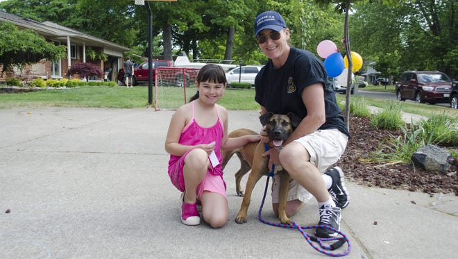 Sarah Shamus, 8, and a second-grader at Parke Lane Elementary School on Grosse Ile, came up with the idea for a kids fun run to benefit the Grosse Ile Animal Shelter. Here, she's with Julie Cortis, the Grosse Ile Police Department's animal control officer, and her rescue dog, Hank, during the first ever Kids Fun Run for Paws. Shamus raised more than $1,200 for the shelter.
