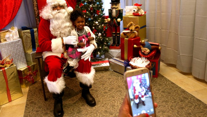 Finally after a half an hour of waiting and trying to figure Santa Claus out, Charli Covington, 1 1/2 of Pontiac, Michigan sits on his lap as her mother Lisa Covington, 39, of Pontiac takes a few pictures. Santa played by Jeryn Calhoun, 59 of Roseville.Santa, played by Jeryn Calhoun, 59 of Roseville, came to visit with kids during the inaugural BLAC Detroit Magazine hosting of Santa at their office turned winter wonderland in Ferndale, Michigan on Saturday, December 12, 2015.Northland Mall, before it closed down earlier this year, use to have a Black Santa Claus for kids to visit and tell him what they wanted for Christmas.With the mall now closed parents who wanted their kids to see a Black Santa had nowhere to go. BLAC Detroit and AT&T stepped in to arrange for Santa to come to their offices in Ferndale on Woodward Avenue.400 families had pre registered for the Saturday mid morning and afternoon event.