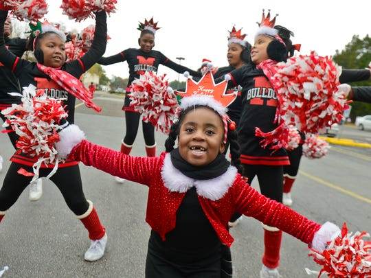 Makenzie Harvey, 3, gets warmed up with members of the Memphis Bulldog's cheer squad before marching down Elvis Presley Boulevard during the 16th annual Whitehaven Christmas Parade on Nov. 23, 2013. Cool temperatures greeted spectators and around 900 entrants. (Chris Desmond/Special to The Commercial Appeal)