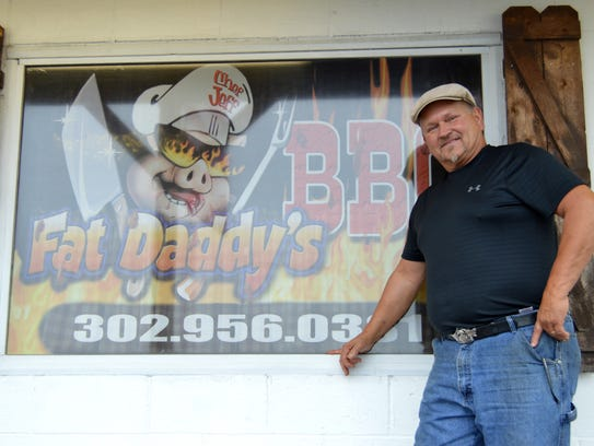 Jeffrey Frey smiles in front of his barbecue eatery,