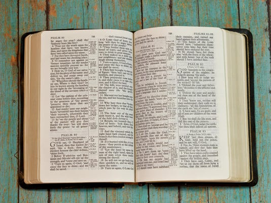 Bible Opened to Psalm on wooden plank background