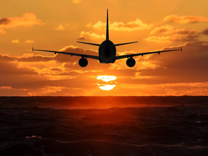 A plane flying in a sunsetting sky