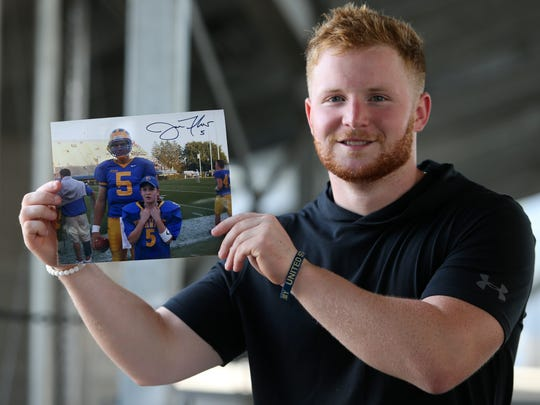 Delaware defensive back Pat Crowley grew up around Blue Hen football. The redshirt junior holds a photo of himself with Delaware quarterback Joe Flacco from 10 years ago.