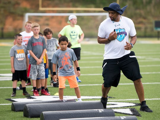 Former Vols defensive end DeAngelo Lloyd works a drill with children at the Legends of Tennessee football camp Thursday at Northview Academy in Kodak.