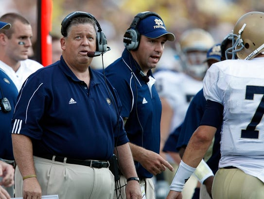 Notre Dame head coach Charlie Weis, left, looks up
