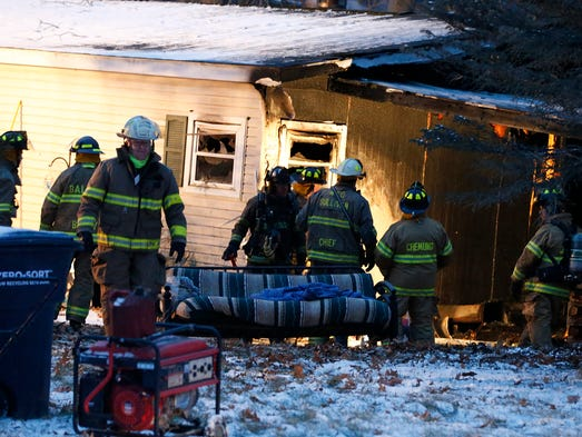 Fire crews work to extinguish and clear a mobile home
