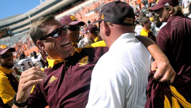 Central Michigan's athletic director Dave Heeke, left, celebrates with CMU head coach John Bonamego after the team's 30-27 win over Oklahoma State in Stillwater, Okla., Saturday, Sept. 10, 2016.
