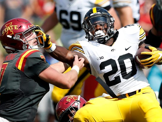 FILE - In this Sept. 9, 2017, file photo, Iowa running back James Butler (20) breaks a tackle by Iowa State linebacker Joel Lanning, left, during the second half of an NCAA college football game in Ames, Iowa. Iowa's 131-yard rushing average is 41 under last year's and lowest since 2012, when the Hawkeyes went 4-8 and won two conference games. (AP Photo/Charlie Neibergall, File)