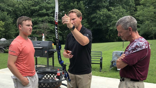 Doug Denton of Hoyt Archery, center, helps Dalton Hinkle set up the Olympic recurve bow that Hinkle won as a prize for finishing first in the NASP National Championships.