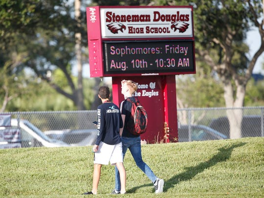 Student walk to class at Marjory Stoneman Douglas High School, Aug. 15, 2018, in Parkland, Fla. Students at the school returned to a more secure campus as they began their first new school year since a gunman killed 17 people in the freshman building.