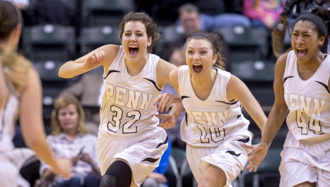 Penn players (from left) Claire Carlton, Kaitlyn Marenyi and Kamra Solomon rush onto the court Saturday night after the final buzzer in the Indiana High School girls' Class 4A state basketball championship against Columbus North. Penn won 68-48.
