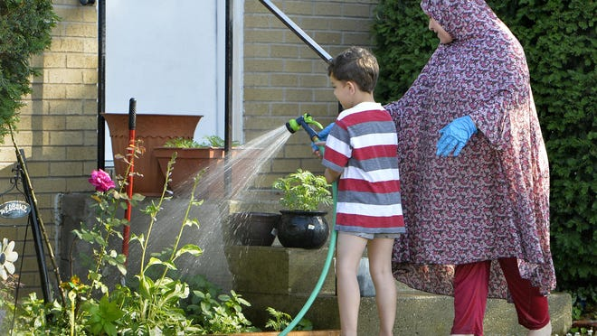 Six-year-old Ali Khuda Raheem helps his mother Fadieh Mahasneh, 42, water plants in front of their Erie home on Wednesday.