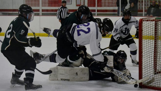 John Jay forward Brian Daley (22) crashes in on Brewster/Yorktown goalie Christian Grossi Sunday in the second period of a 7-4 win over Brewster/Yorktown at BIA.