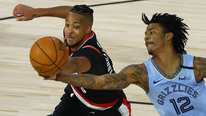 Portland's CJ McCollum and Memphis' Ja Morant (12) go after a rebound during the fourth quarter of Saturday's game. McCollum scored 14 of his 29 points in the fourth quarter as the Trail Blazers rallied for a 126-122 win.