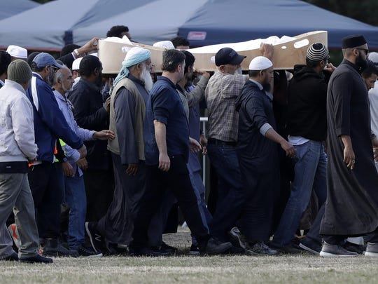Mourners carry the body of a victim of the Friday, March 15, mosque shootings for burial at the Memorial Park Cemetery in Christchurch, New Zealand, Wednesday, March 20, 2019.