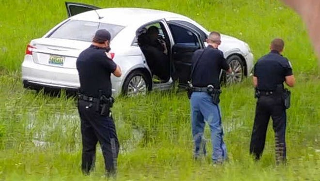 A video Frame grab shows police in a standoff with an armed robbery suspect in the median of I-10 in Hancock County on Sunday.