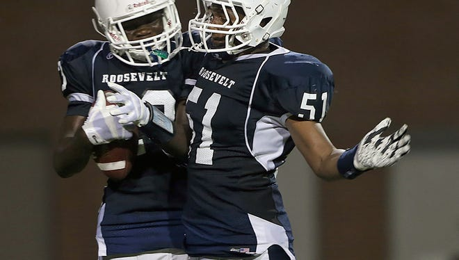 After scoring touchdown on a pass reception, Roosevelt's Prince Krah, left, celebrated with John Hawkins, in Friday's win over East at Drake Stadium.